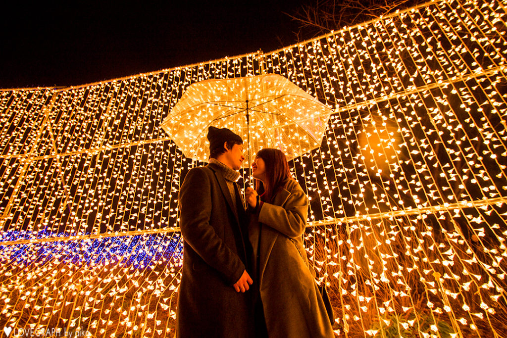 Image of a Japanese couple in front of a Christmas light display