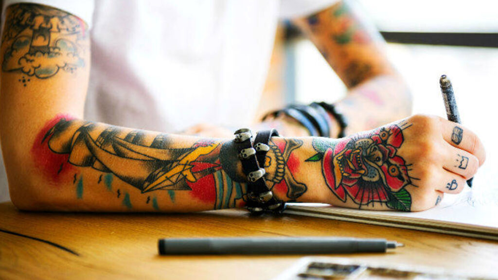 Close up image of a person with coloured arm tattoos.