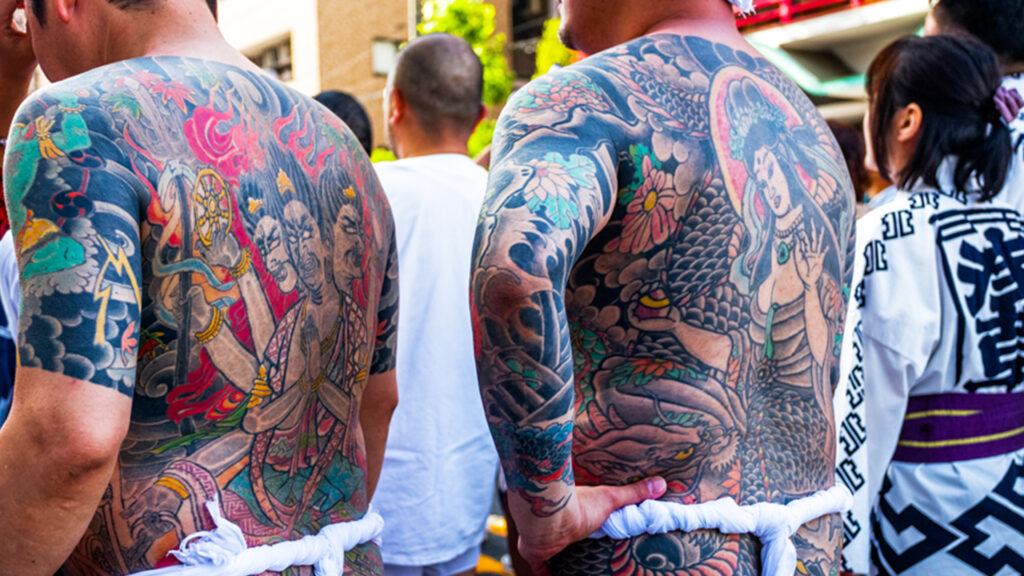 Image of two people with coloured body tattoos.